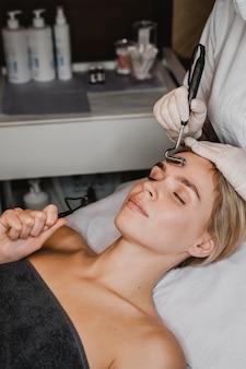 Mujer joven recibiendo un tratamiento facial