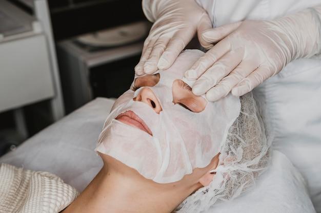 Mujer joven recibiendo un tratamiento de mascarilla para la piel en el spa
