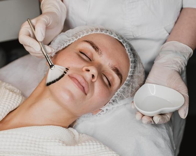 Mujer joven recibiendo un tratamiento para la piel de la cara