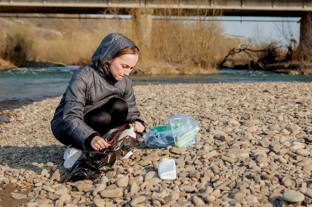 Mujer joven recogiendo basura plástica de la playa y metiéndola en bolsas de plástico negras para su reciclaje. concepto de limpieza y reciclaje.