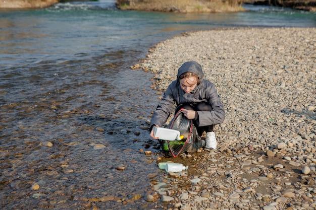 Mujer joven recogiendo basura plástica de la playa y ponerla en bolsas de plástico negro para su reciclaje. concepto de limpieza y reciclaje.