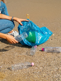 Mujer joven recogiendo botellas de plástico reciclables en la playa.