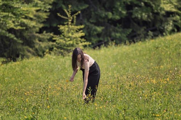 Mujer joven recogiendo flores en un prado.