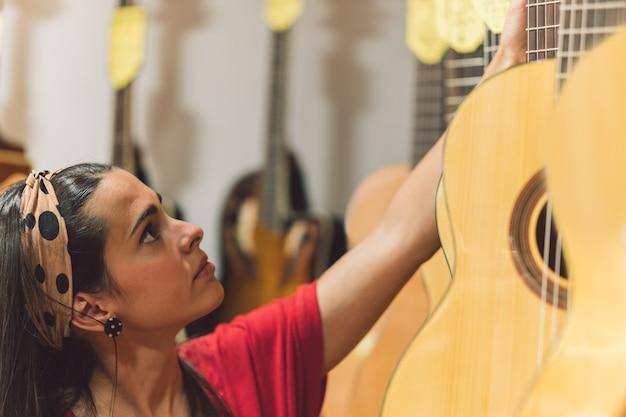 Mujer joven recogiendo una guitarra colgada en una tienda con otras guitarras.