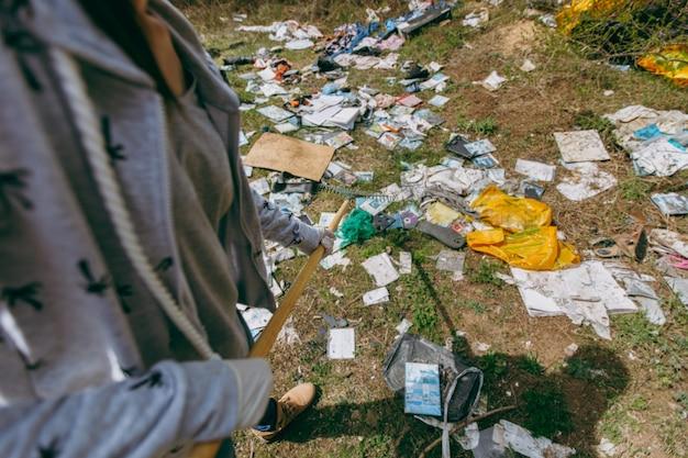 Mujer joven recortada en ropa casual, guantes para limpiar con rastrillo para la recolección de basura en el parque lleno de basura