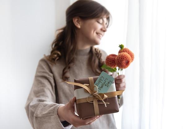 Mujer joven con un regalo para el día de la madre y un ramo de flores en sus manos
