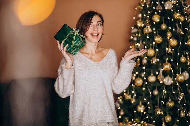 Mujer joven con regalo de navidad junto al árbol de navidad