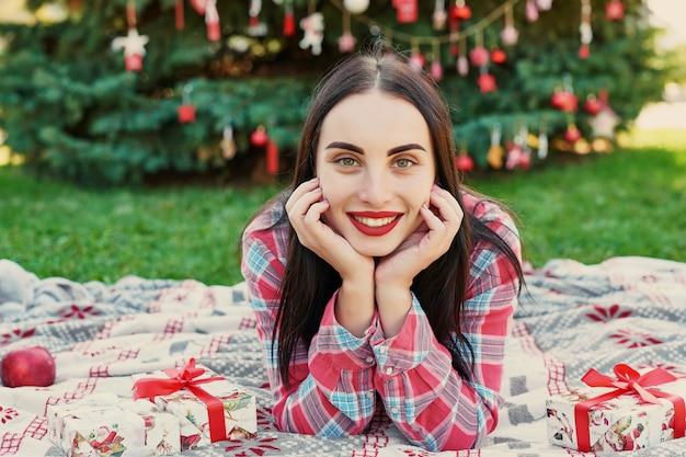 Mujer joven con regalos cerca de un árbol de navidad, navidad en julio en la naturaleza