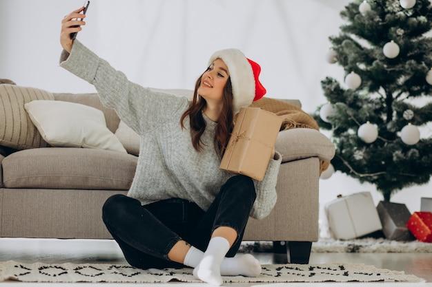 Mujer joven con regalos de navidad por el árbol de navidad