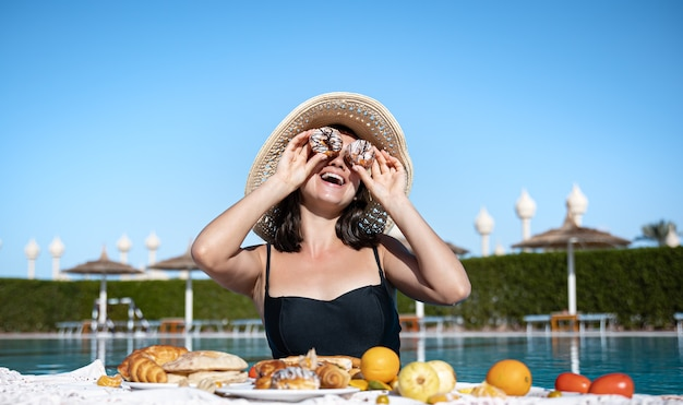 Mujer joven se regocija con la deliciosa comida cerca de la piscina