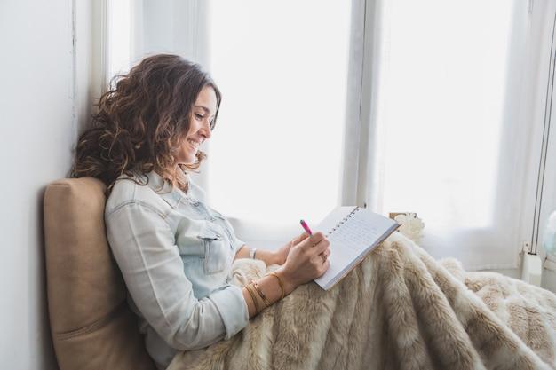 Mujer joven relajada escribiendo en su cuaderno