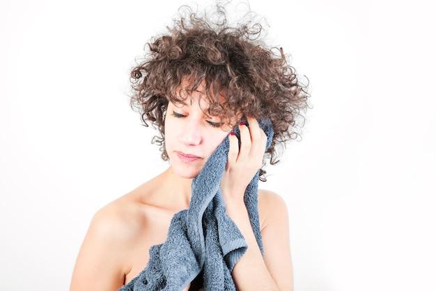 La mujer joven relajada limpia su cara con la toalla contra el contexto blanco