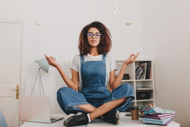 Mujer joven relajada con piel bronceada sentada en posición de loto sobre la mesa con ordenador portátil y documentos
