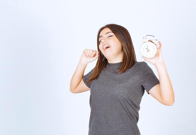 Mujer joven relajada en pijama con un despertador bostezando y de pie.