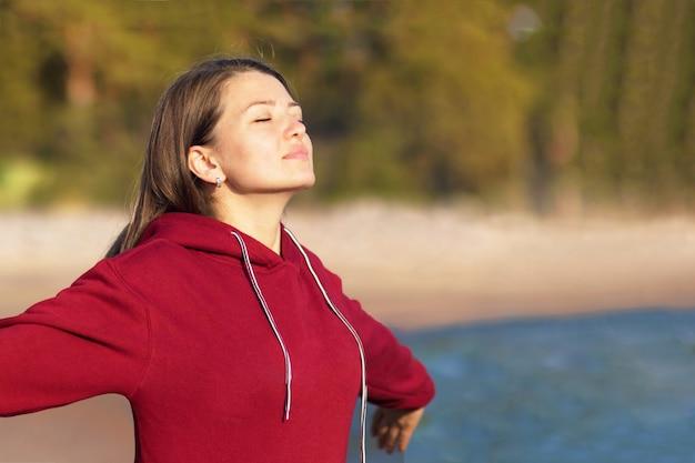 Mujer joven relajada respira aire fresco en la naturaleza en la playa