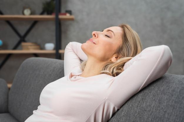 Mujer joven relajada sonriente que inclina su cabeza en el sofá