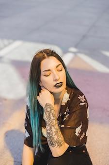 Mujer joven relajada con el tatuaje en su mano