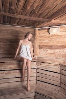 Mujer joven relajada en toalla envuelta que se sienta en banco de madera en la sauna