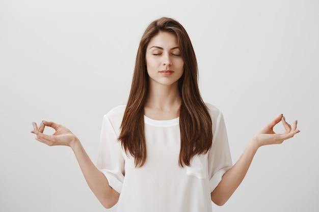 Mujer joven relajada y tranquila meditando con las manos extendidas hacia los lados