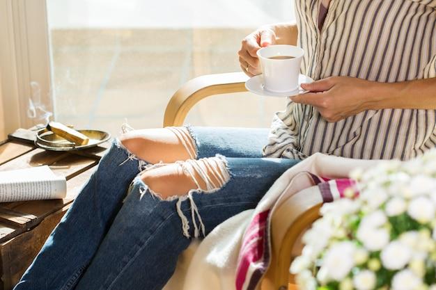 Mujer joven se está relajando en casa bebiendo té libro de lectura