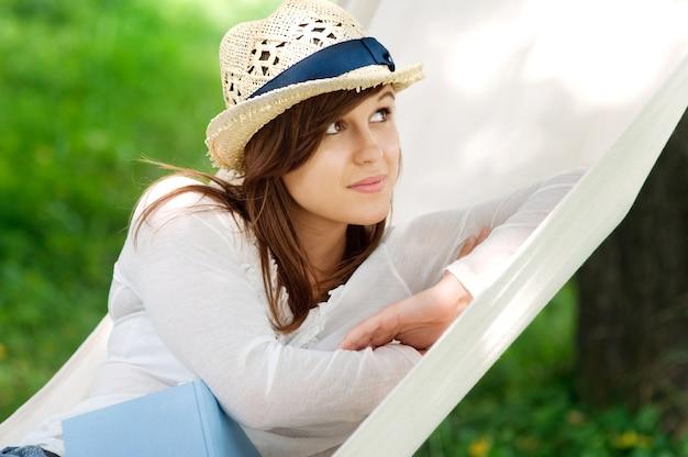 Mujer joven relajándose en una hamaca con libro