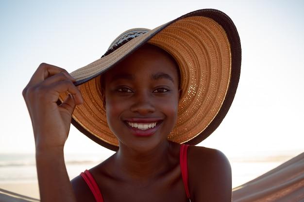 Mujer joven relajándose en una hamaca en la playa