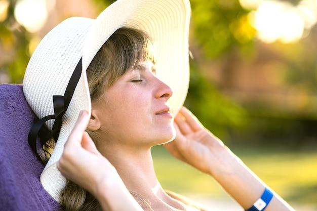 Mujer joven relajante al aire libre en un día soleado de verano. señora feliz acostada en la cómoda silla de playa soñando pensando. calma hermosa niña sonriente disfrutando del aire fresco relajándose con los ojos cerrados.
