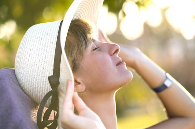 Mujer joven relajante al aire libre en un día soleado de verano.