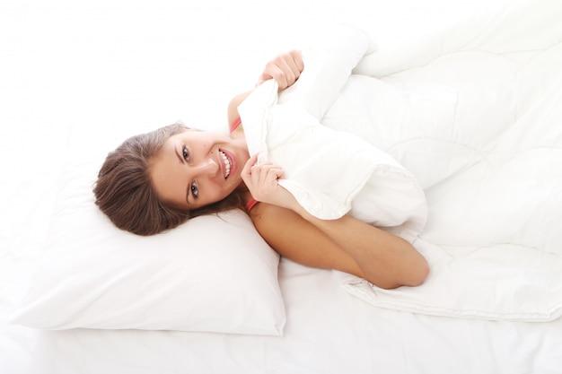 Mujer joven relajante en la cama por la mañana