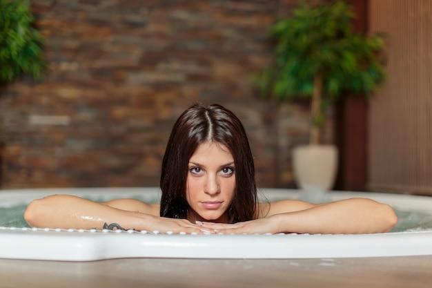 Mujer joven relajante en el jacuzzi