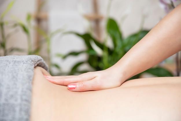 Mujer joven relajante durante el masaje de espalda en el spa