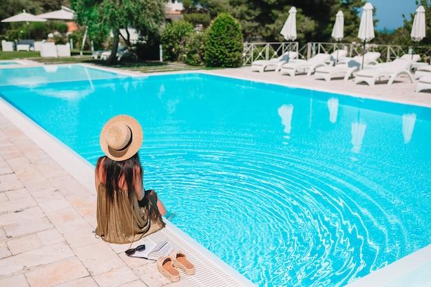 Mujer joven relajante en la piscina de un hotel de lujo