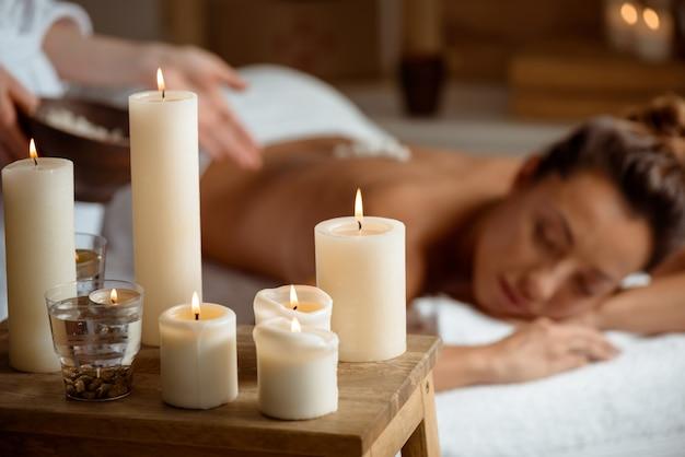 Mujer joven relajante en el salón de spa. centrarse en velas.