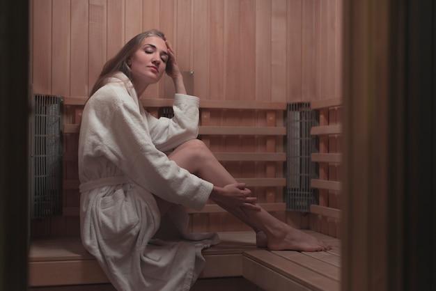 Mujer joven relajante en una sauna de madera