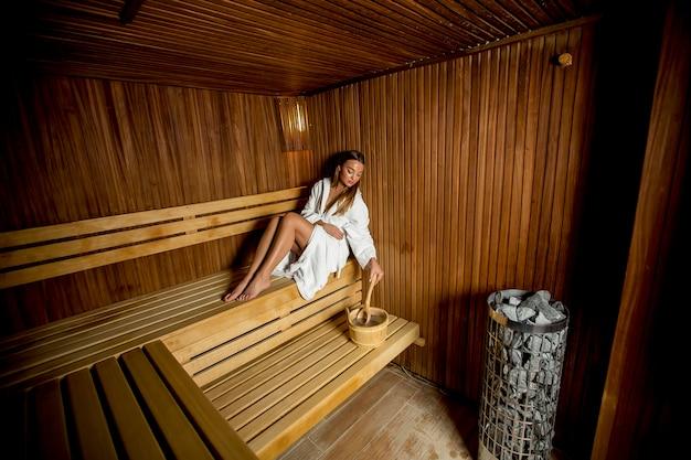 Mujer joven relajante en la sauna