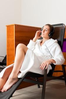 Mujer joven relajante en spa con música