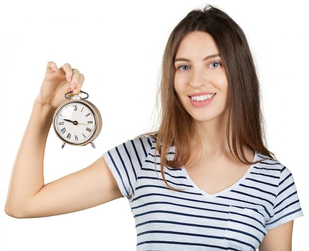 Mujer joven con el reloj de alarma aislado en blanco. concepto de gestión del tiempo