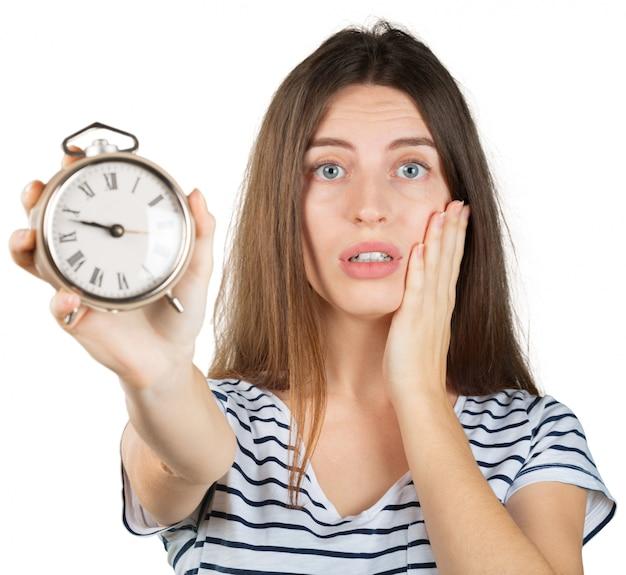 Mujer joven con el reloj de alarma aislado en blanco, concepto de la gestión de tiempo