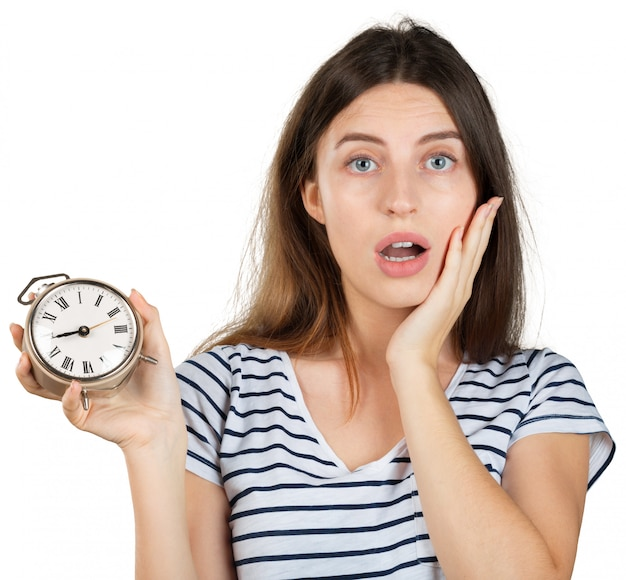Mujer joven con el reloj de alarma aislado en blanco