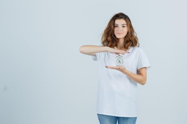 Mujer joven con reloj despertador en camiseta blanca, jeans y aspecto alegre. vista frontal.