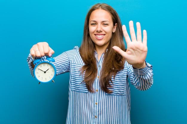 Mujer joven con reloj despertador contra azul