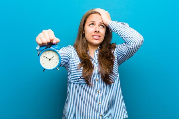 Mujer joven con reloj despertador contra el fondo azul.