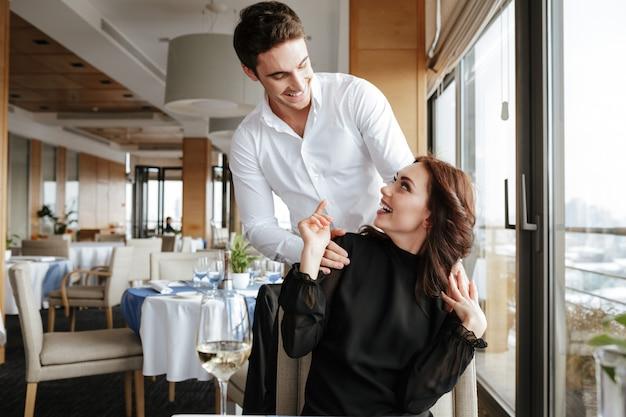 Mujer joven en restaurante con hombre detrás de ella