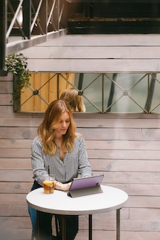 Mujer joven revisando correos electrónicos en su tableta
