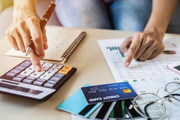 Mujer joven revisando facturas, impuestos, saldo de cuenta bancaria y calculando gastos de tarjeta de crédito en casa