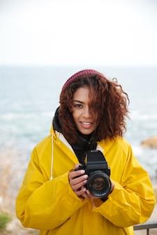 Mujer joven rizada africana alegre que lleva la capa amarilla que sostiene la cámara.