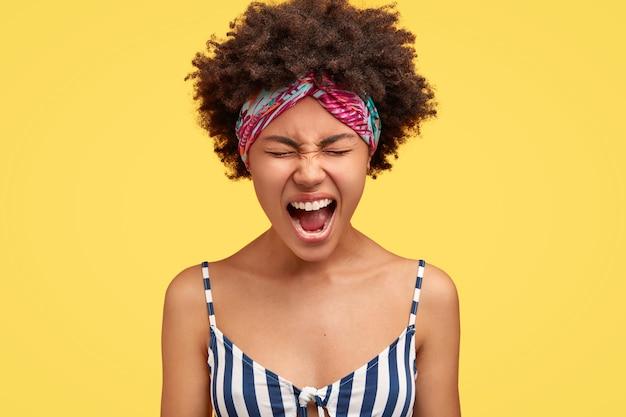 Mujer joven rizada atractiva furiosa con piel oscura, abre la boca mientras grita con enojo, parece enojado