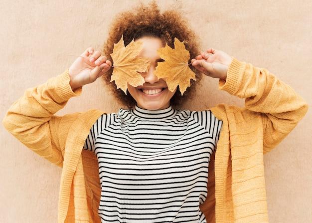 Mujer joven rizada que cubre sus ojos con hojas