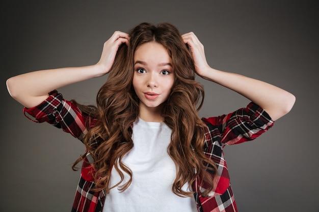 Mujer joven rizada sorprendida que se coloca con las manos en la cabeza