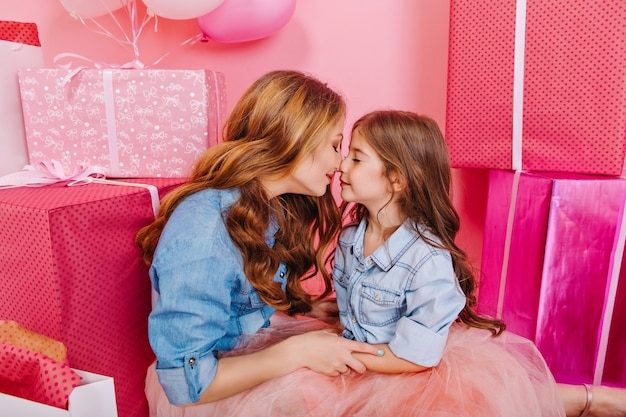 Mujer joven rizada en traje retro de la mano de la hija sentada en el suelo junto a las cajas presentes y globos de helio. retrato de cumpleañera y su mamá linda posando en la fiesta con regalos